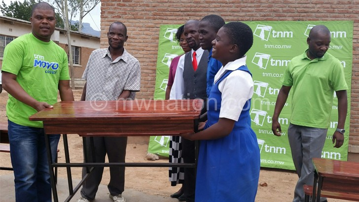 Chimpeni symbolically donating a desk to the school.