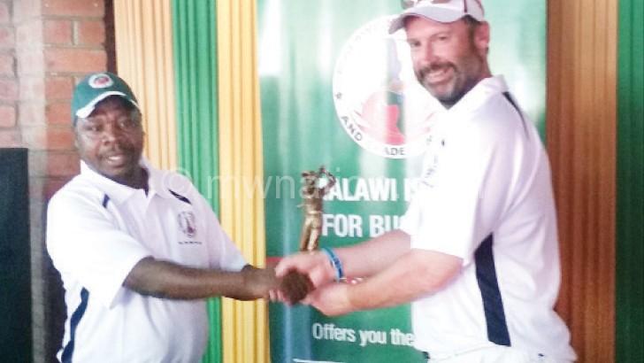 Phiri (L) receives his trophy from British Ambassador Michael Nevin