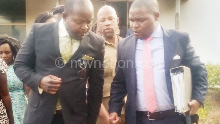 Mphwiyo (L) consults his lawyer at the court