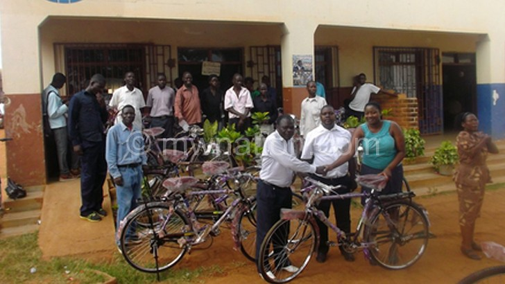 Nsongolo (R) handing over a  bicycle to a benficiary