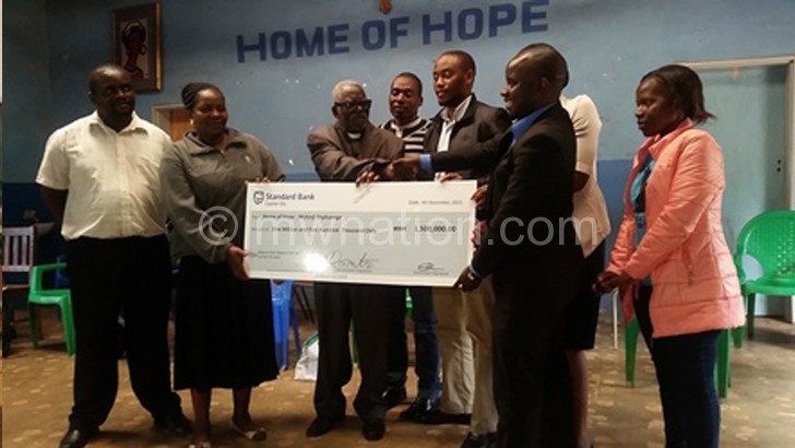 Chipeta (3rd from L) receives the bursaries during the  symbolic handover ceremony