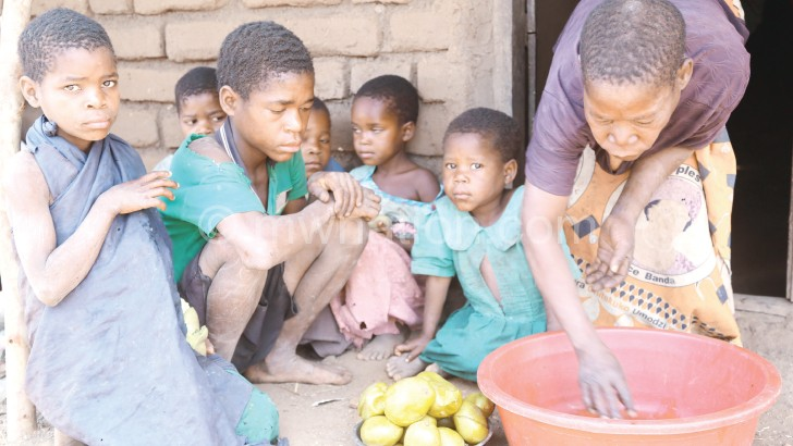 Chilumpha and her children share some cooked mangoes