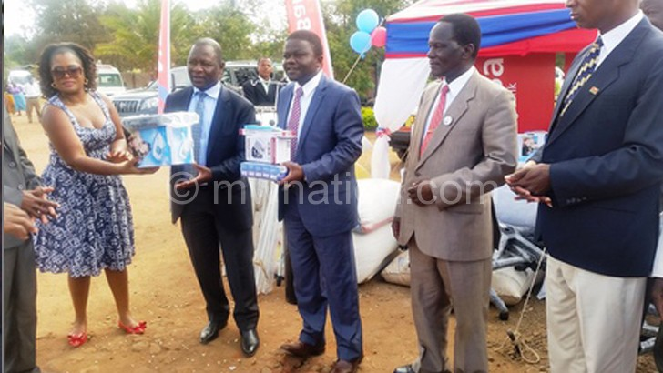 Kumpalume (in navy blue suit) receives some equipment  from NBS Bank officials