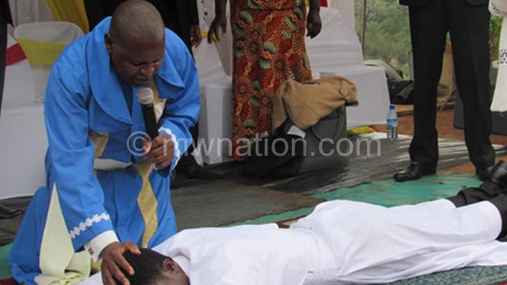 Sodzera (in blue) making declarations as he ordains Salinga lying down