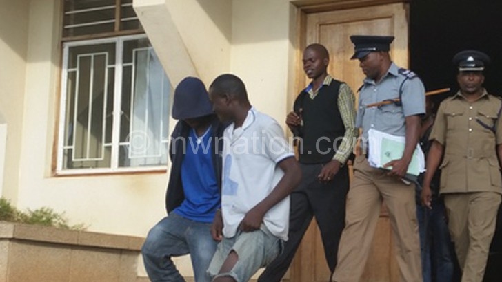 Ngulube (in white golf shirt)  being led to jail