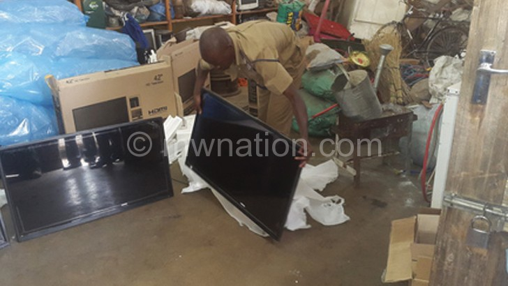 Limbe Police assistant spokesperson Widson Nhlane unwrapping a TV set