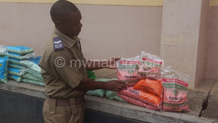Limbe Police Station deputy spokesperson Pedzisai Zembeneko shows the reporter some of the confiscated fake seeds