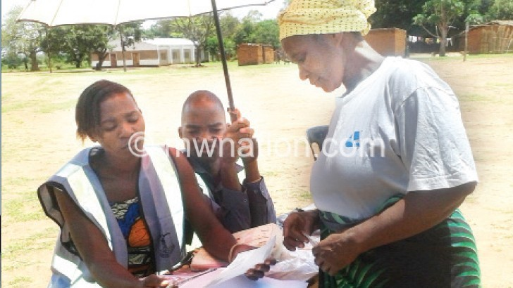 A voter (R) gets a brief on how to mark a ballot paper in Mchinji