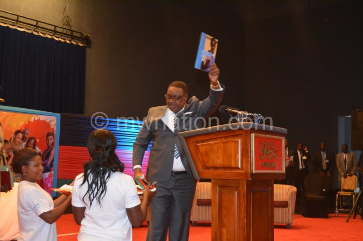 Mutharika shows off a booklet he received from  the youth at the conference