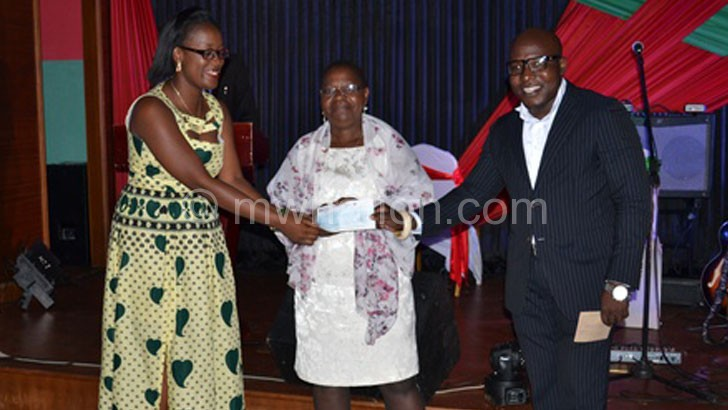CHRR board chair Charity Salima (L) and her execuive director Timothy Mtambo (R) hands over cheque to Laura Munthali