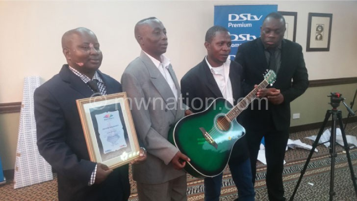 Nyirenda (R), Maliro (L) and two members of the band pose with the guitar and certificate