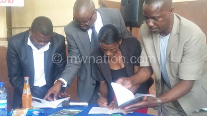 Kasunda (in spectacles) going through the charter with colleagues
