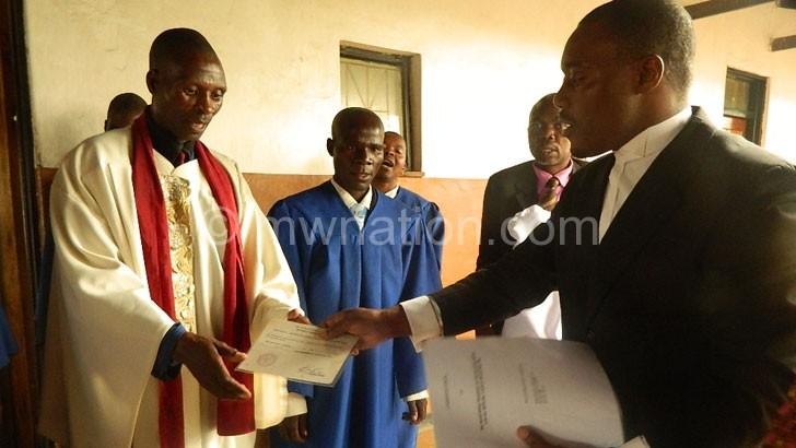 Lumwira (R) hands over power to Tambala