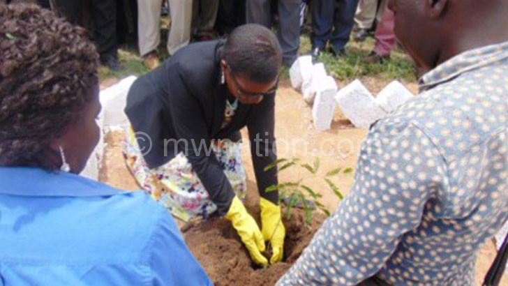 Botomani plants her tree during the event