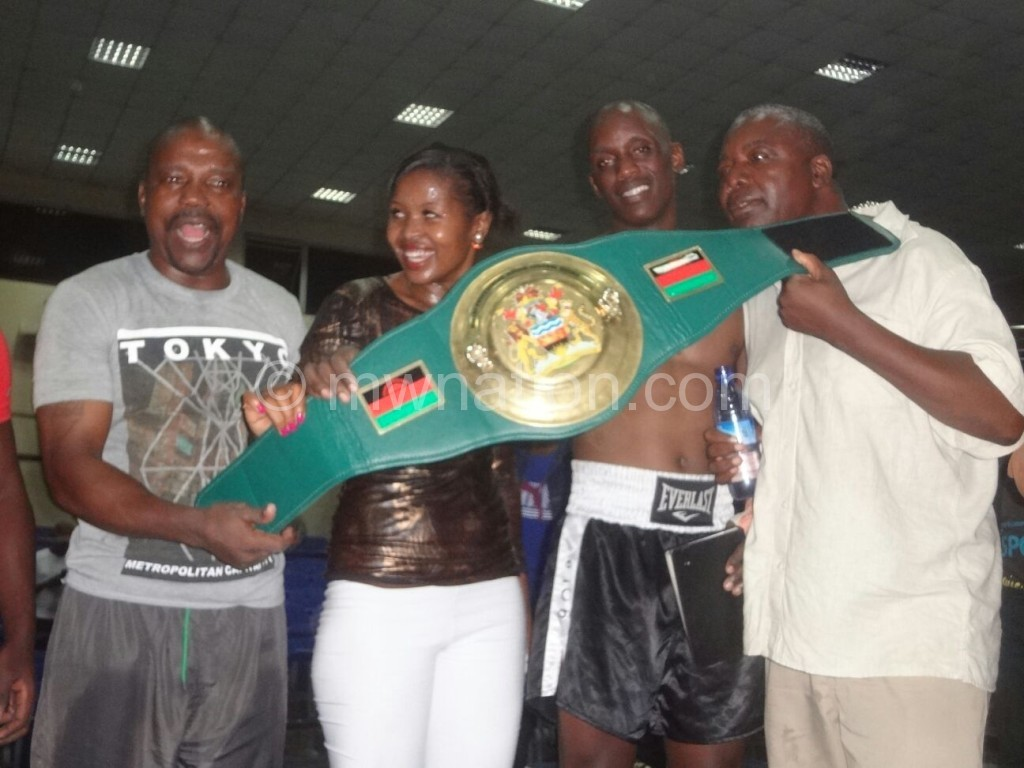 Mwando flanked by his wife Agnes (2ndL) and promoter Robin Alufandika (R) display his belt