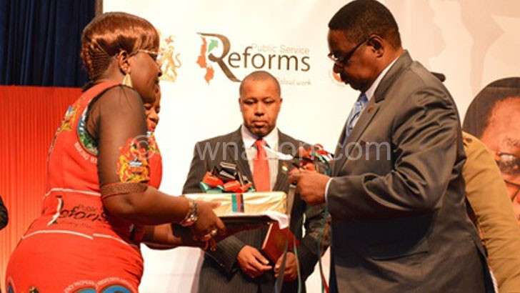 Mutharika being presented with the reforms documents from the reform team