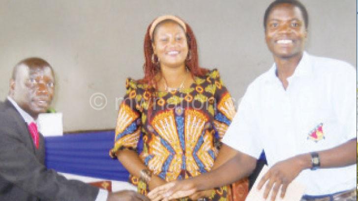 Mwale handing over an award to a student as Kainga looks on