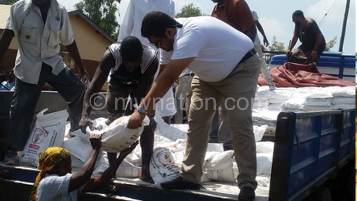 A Bilal Trust official (R) donating a bag of flour to beneficiaries