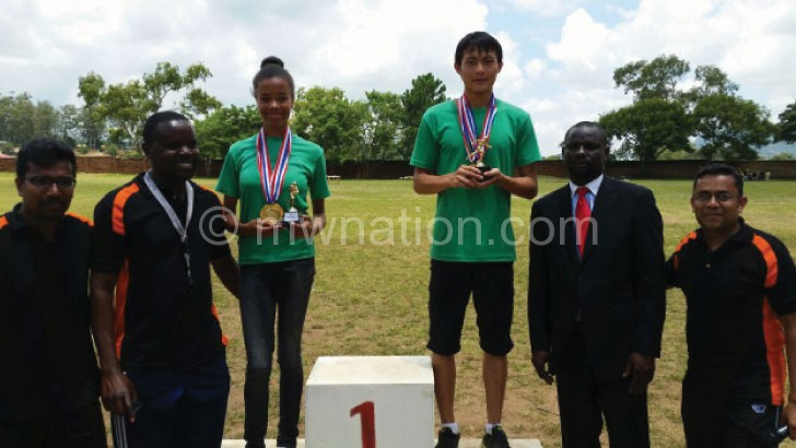 Yan and Kamange show their medals while posing with sports and Central High officials
