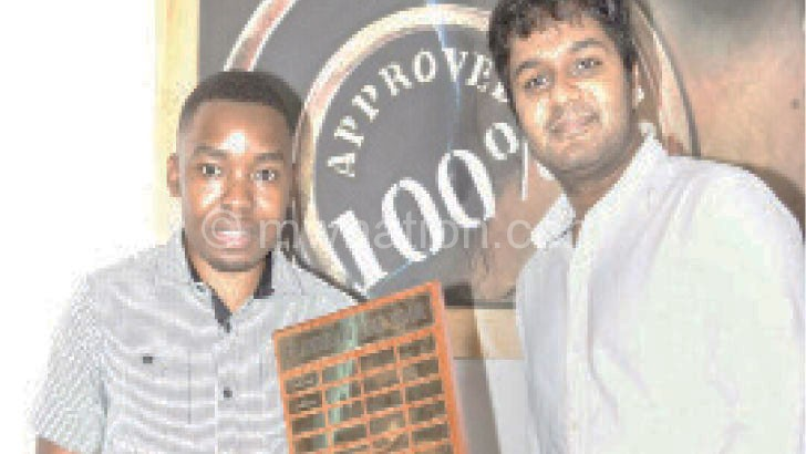 Mwale (L) receiving his trophy from Glenwood chess president Sayen Naidoo