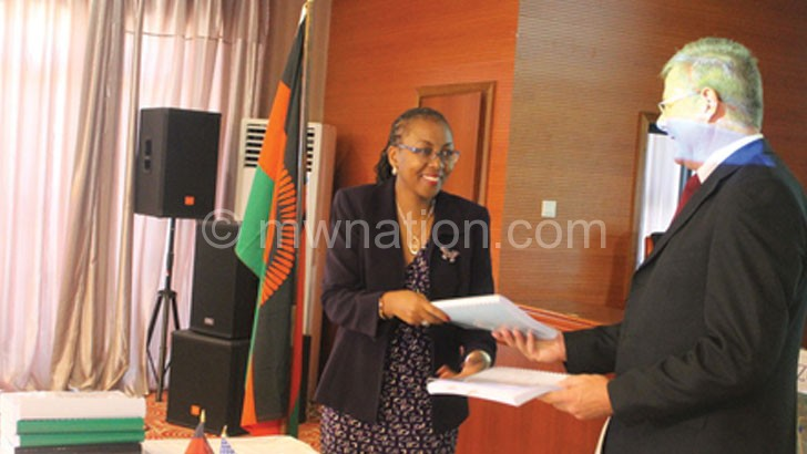 Banda (L) and Bushney exchanging documents