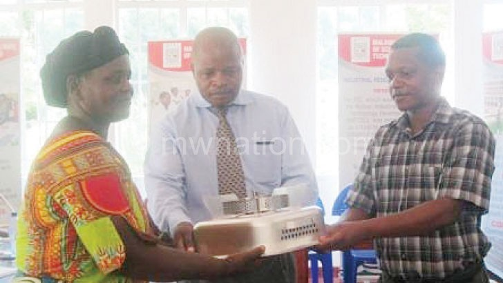 Mweta(R) handing over a stove to Mhango (C)and a beneficiary