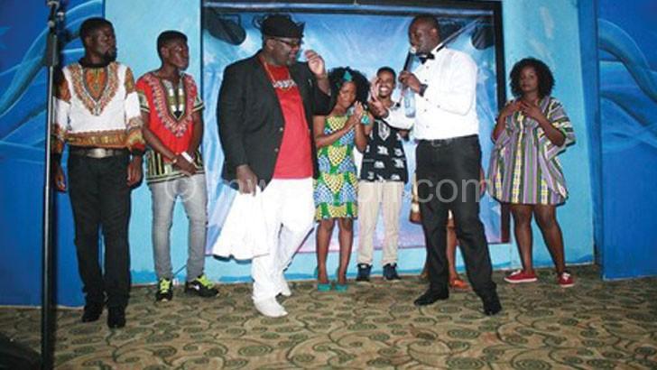 Lucius Banda interacting with MC Rob Kalua as the contestants await their turn