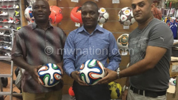 Ismail (R) hands over the matchballs to Missi (C) as SR member Billy Tewesa looks on