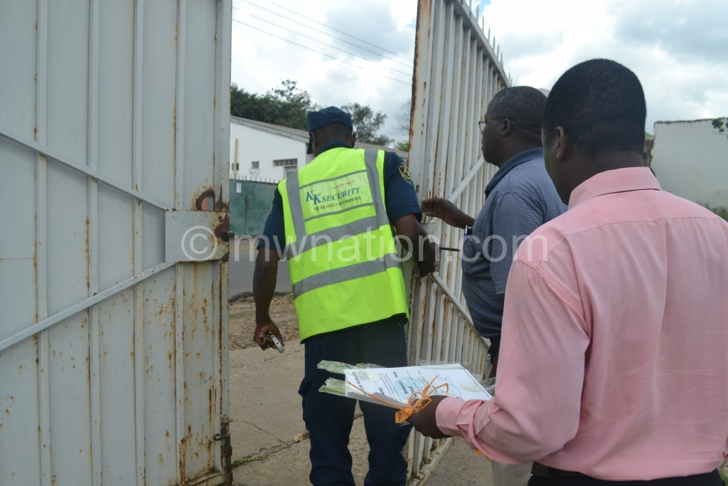 A security guard opens the gate after MRA officials cut the seal