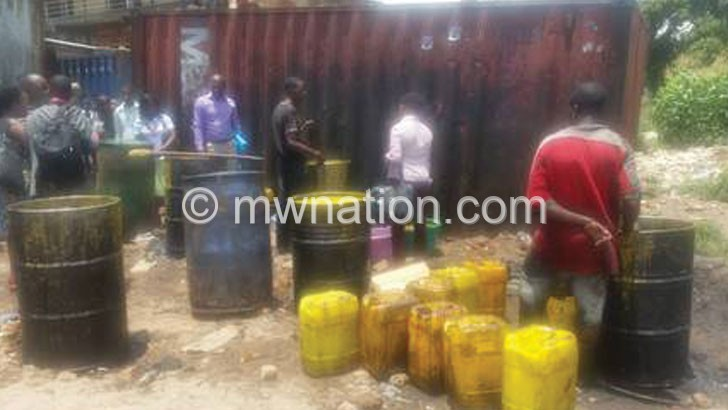 An employee found manually purifying oil behind Limbe Market