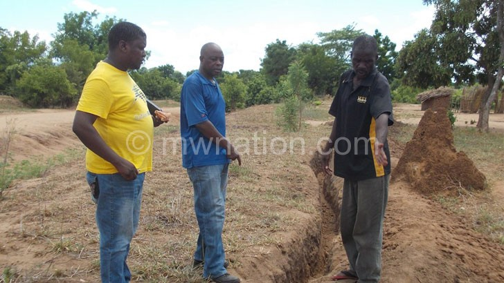 Caption: Nsamba are VDC chair Peter Samson (R) showing Msowoya (M) and Card irrigation officer Mike Mwale (L) where the pipes will pass.JPG --