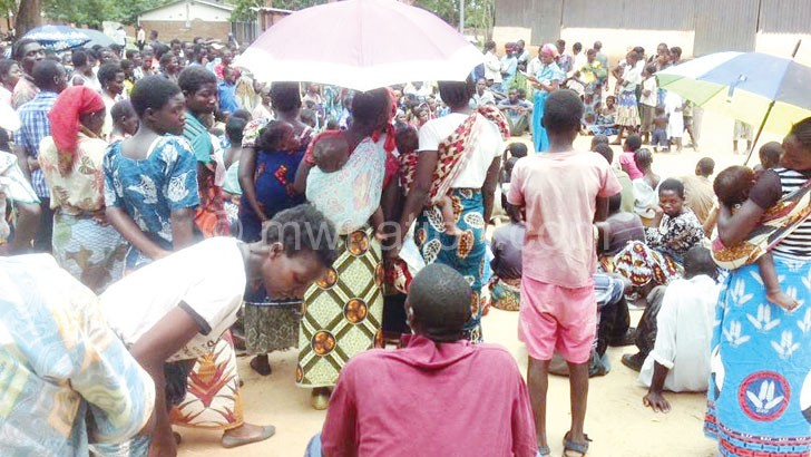 People wait for their turn to buy maize at an Admarc depot where prices are lower than those offered by private traders