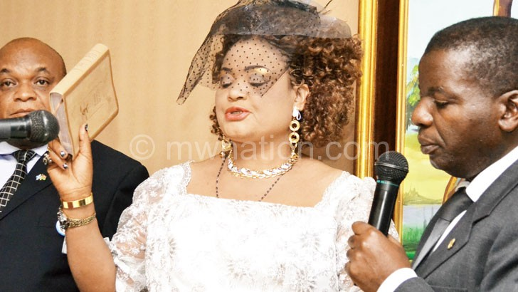 Gender Minister Patricia Kaliati takes oath of office as her husband (L) looks on