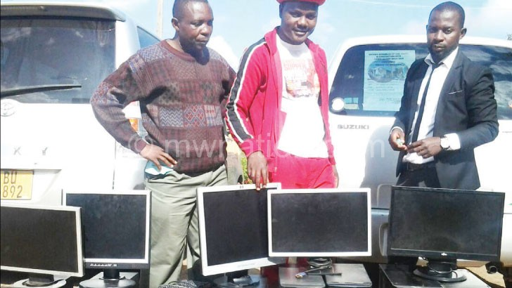 Music Union of Malawi and Cosoma officials stand before the confiscated computers