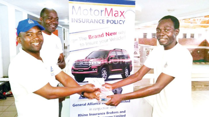 Well done: Matewere (R) receives his trophy from Kapesa (L) as Kawaye looks on