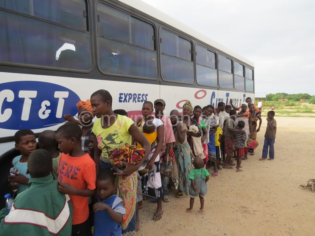 Some of the asylum seekers queue to board a bus to the camp