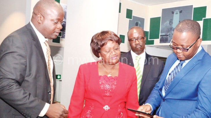 Limbe Branch client service manager MacDonald Chibwe (R) demonstrating free WI-FI on tablets to Ngwira (C) as Stanley Mkwamba (L) and Maziko Sauti-Phiri look on