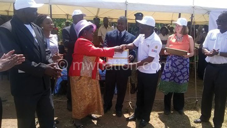 Kumpalume (R) handing a certificate to Kayembe  as other officials look on