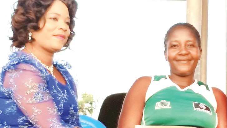 Amos (L) presents a cheque to blantyre Stars captain Ruth Kaipa-Chimombo