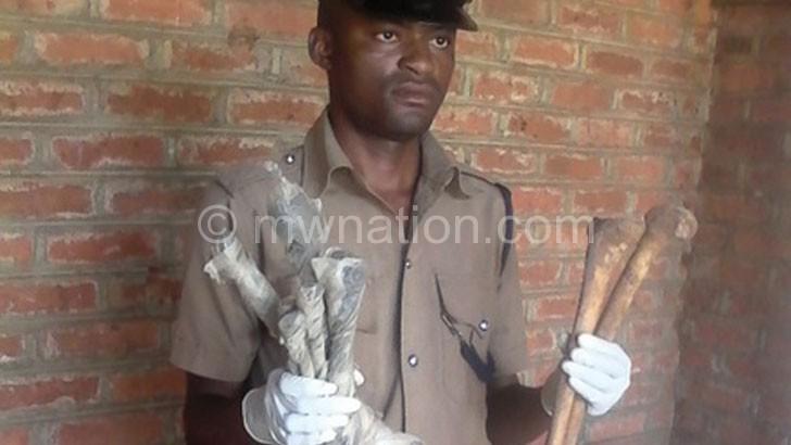 Sulumba holding bones of people  with albinism