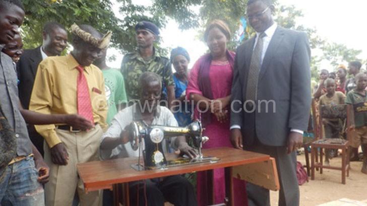 GVH Balaka (seated) testing a sewing machine as Ndau (L) and others watch