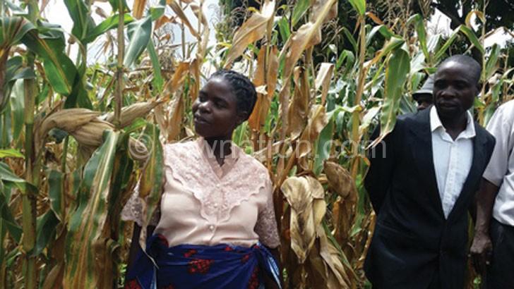 A farmer (L) admiring maize in her garden