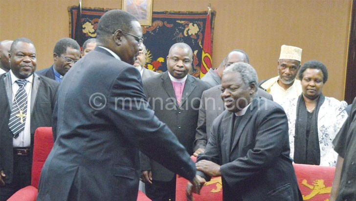 Mutharika shakes hands with PAC chairperson the Very Reverend Felix Chingota at the meeting