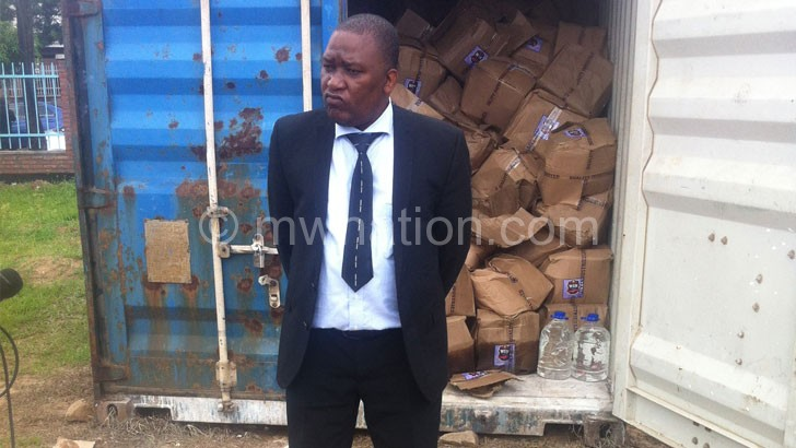 stephen-kuyeli standing infront of one of the containers containing the alcohol