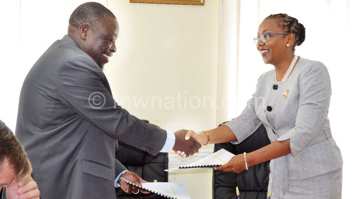 Ndawala (L) and Banda exchange PCA documents after signing the deal