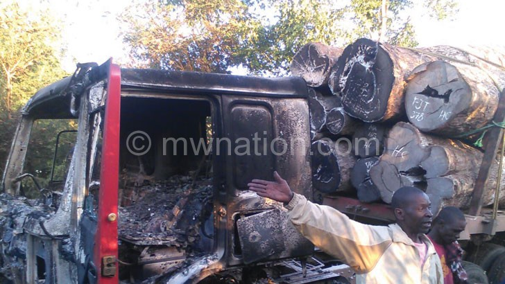 The charred remains of the truck carrying round wood in Mozambique