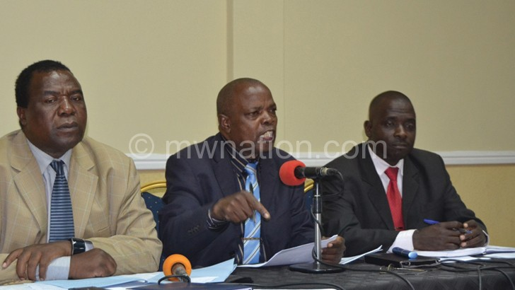Muwake (C) stresses a point as Kalekeni (L) and another member look on