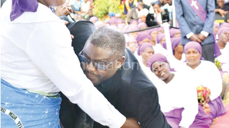 Mabedi's wife supports him after laying a wreath  on Nyanga's grave