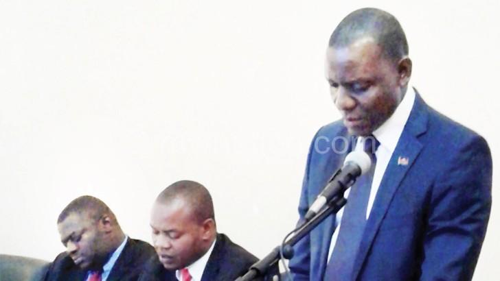 Kasaila speaks as Mkwezalamba (L) and Chileka-Banda take notes