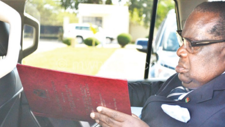 Gondwe takes a last glance at the budget document  as he arrives at Parliament on Friday